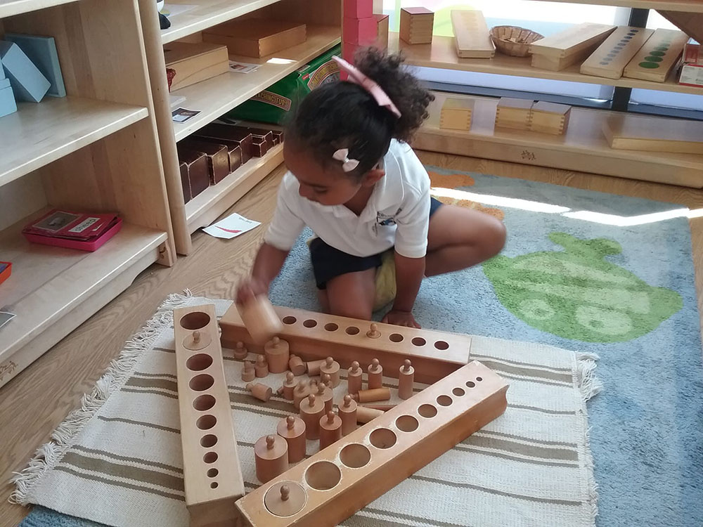 happy girl playing with wooden blocks at a Preschool & Daycare Serving Colindale, Edgware & St Albans UK