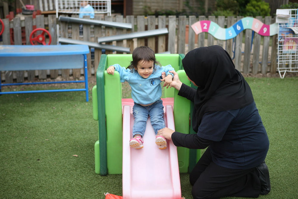 teacher and happy toddler playing in playground at a Preschool & Daycare Serving Colindale, Edgware & St Albans UK