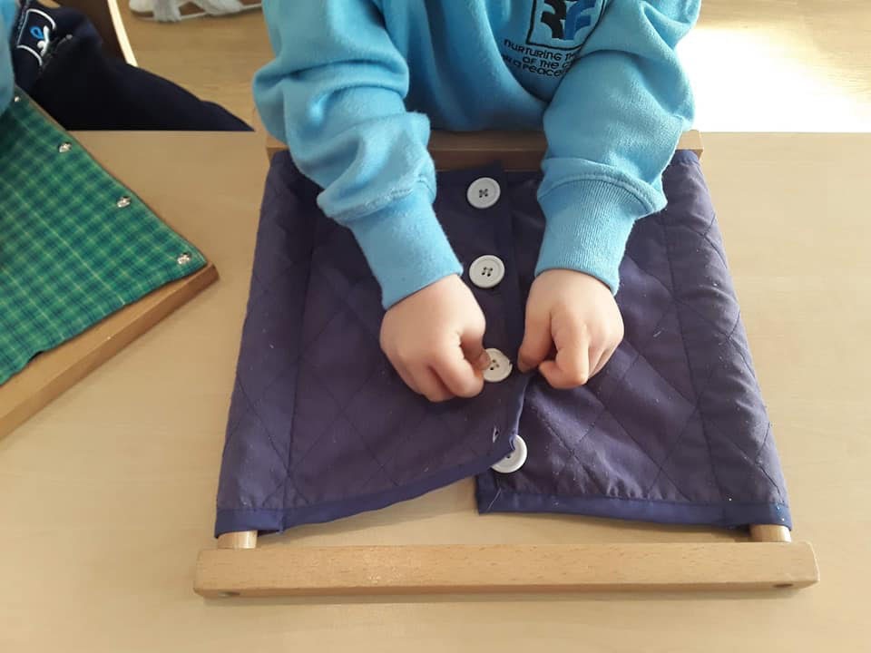 toddler learning to button a shirt at a Preschool & Daycare Serving Colindale, Edgware & St Albans UK