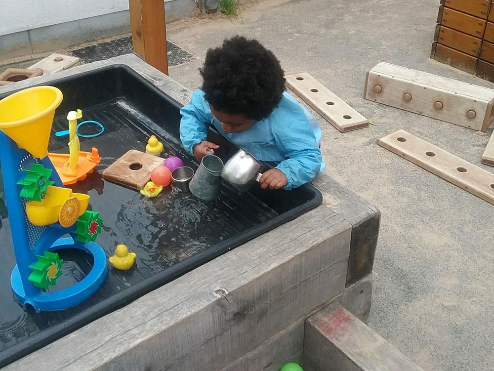 cute baby playing with toys in water at a Montessori Pre-school and Nursery Serving Colindale, Edgware & St Albans UK