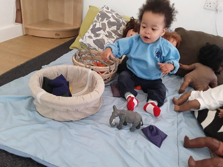 cute smiling baby playing at a Montessori Pre-school and Nursery Serving Colindale, Edgware & St Albans UK