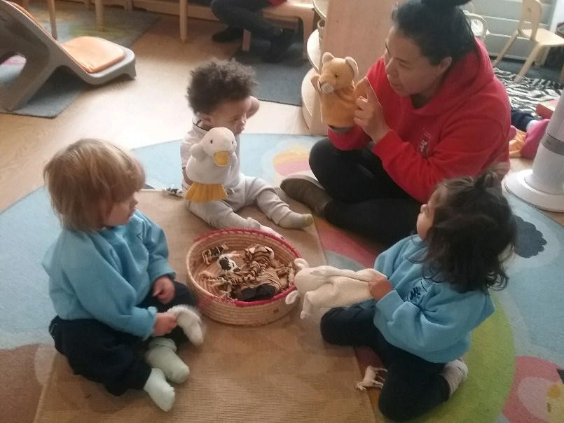 teacher and babies playing with hand puppet at a Montessori Pre-school and Nursery Serving Colindale, Edgware & St Albans UK