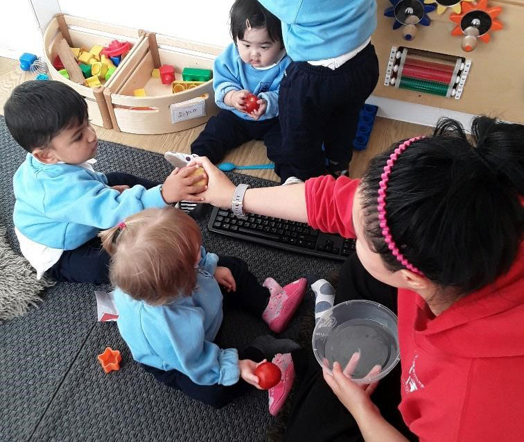 teacher and babies playing with toys at a Montessori Pre-school and Nursery Serving Colindale, Edgware & St Albans UK