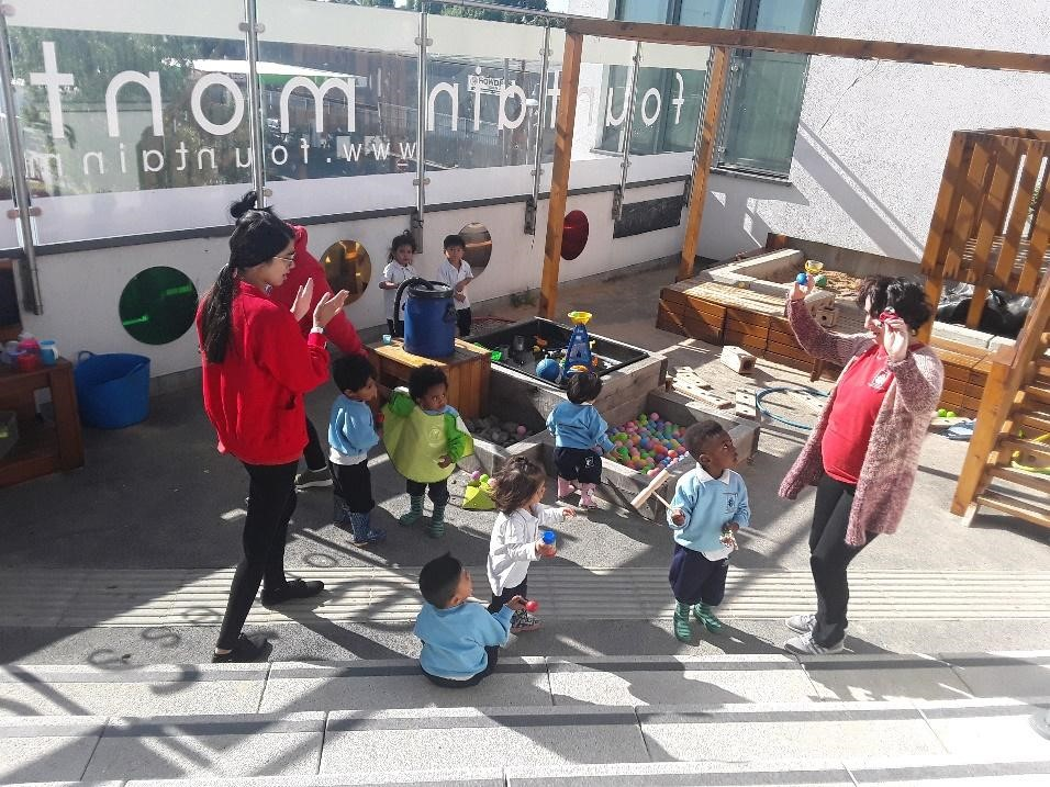teachers and children playing outdoors at a Montessori Pre-school and Nursery Serving Colindale, Edgware & St Albans UK