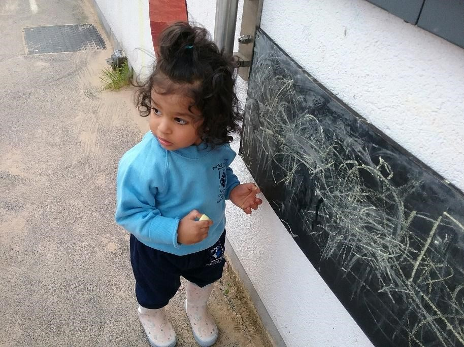 young girl writing on chalk board at a Montessori Pre-school and Nursery Serving Colindale, Edgware & St Albans UK